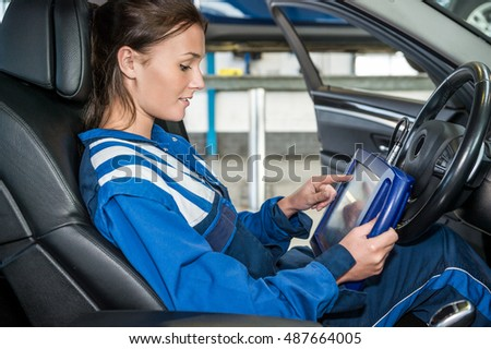 Side view of female mechanics using digital tablet in car at garage