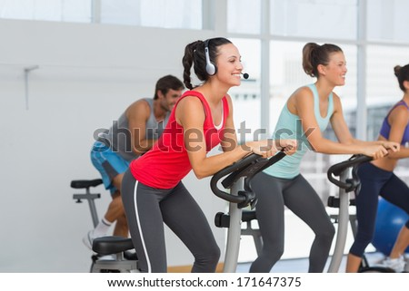 Side view of fit young people working out at class in gym