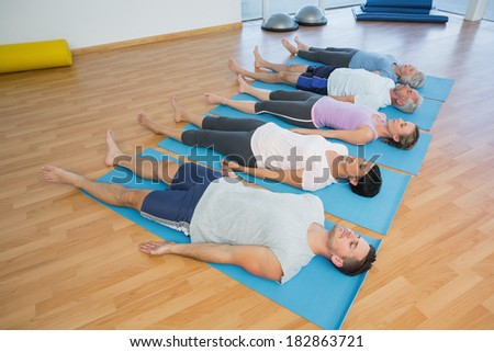 Side view of fitness class resting on mats in row at yoga class - stock photo