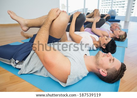 Side view of fitness class stretching legs in row at yoga class - stock photo