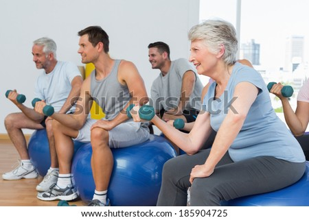 Side view of fitness class with dumbbells sitting on exercise balls in a bright gym