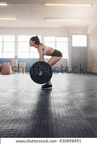 Side view of fitness woman doing exercise with a heavy weights  in gym. Muscular woman practicing weightlifting at health club. - stock photo