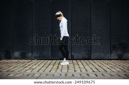 Side view of fitness woman preparing for a city run. Young caucasian woman walking on pavement looking down. - stock photo
