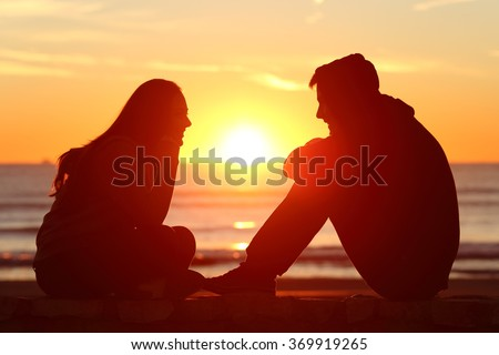 Side view of full body of two friends or couple silhouette of teens facing at sunset on the beach with the sun in the middle - stock photo