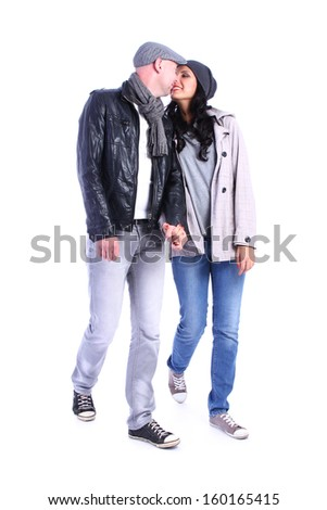 Side view of going young couple (man and woman) . walking girl and guy in jacket and jeans together kissing. Isolated over white background.