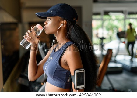 Side view of gorgeous black female athlete drinking water from bottle in the gym - stock photo