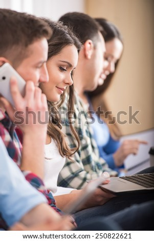 Side view of group of students with laptop, smartphone and book. - stock photo