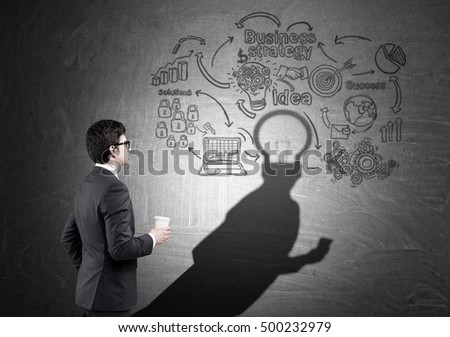 Side view of guy holding paper cup of coffee and looking at shadow of startup sketch on blackboard. His head is a light bulb.