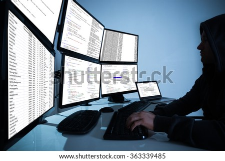 Side view of hacker using computers to steal data in office - stock photo