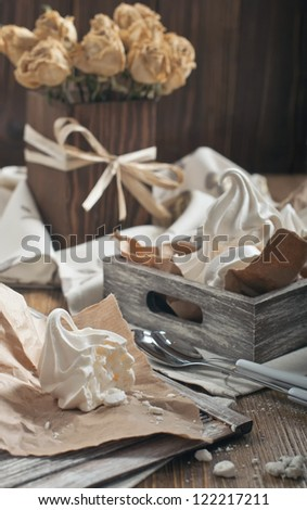 Side view of half of meringue and crumbs on paper, wooden box with meringues and dry roses in square vase on dark wooden background - stock photo