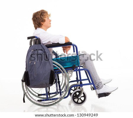 side view of handicapped teen boy sitting on wheelchair - stock photo