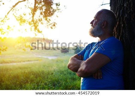 Side view of handsome aged man with white beard standing near the tree and looking at the sunset