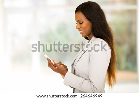 side view of happy african secretary using smart phone - stock photo