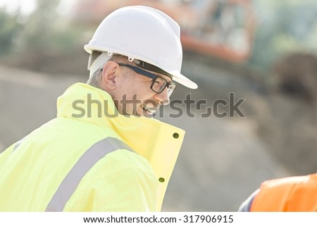 Side view of happy male supervisor at construction site - stock photo