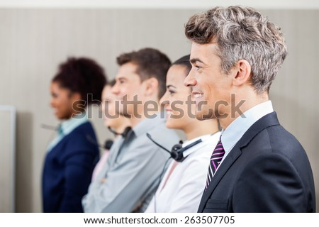 Side view of happy manager standing in row with call center employees at office - stock photo