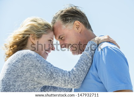 Side view of happy mature couple looking at each other against clear blue sky - stock photo