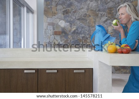 Side view of happy middle aged woman eating apple at kitchen counter - stock photo