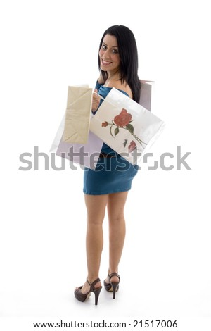 side view of happy model holding carry bags on an isolated background - stock photo
