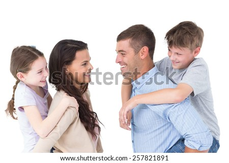 Side view of happy parents giving piggyback ride to children over white background - stock photo