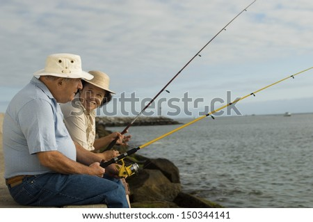 Side view of happy senior couple fishing at the beach - stock photo