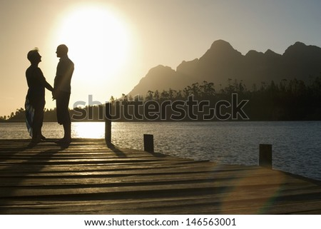 Side view of happy senior couple standing on edge of pier by lake - stock photo