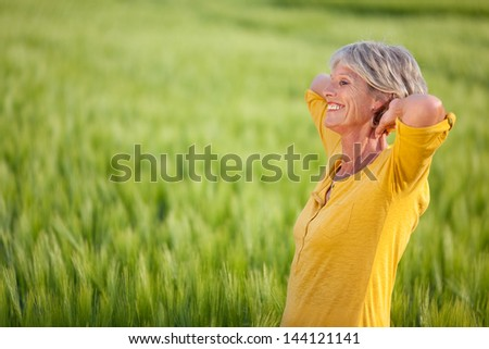 Side view of happy senior woman with hands behind head looking away on grassy field - stock photo