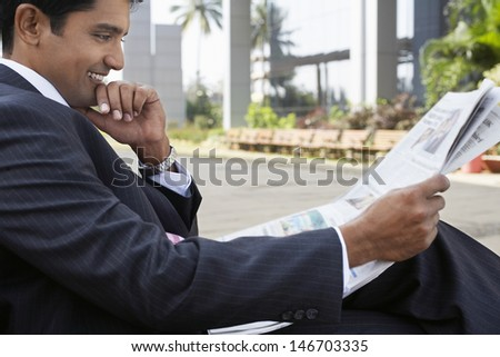 Side view of happy young businessman reading newspaper outdoors - stock photo