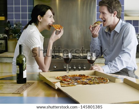 Side view of happy young couple eating pizza in kitchen - stock photo