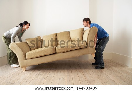 Side view of happy young couple placing sofa in living room of new home - stock photo