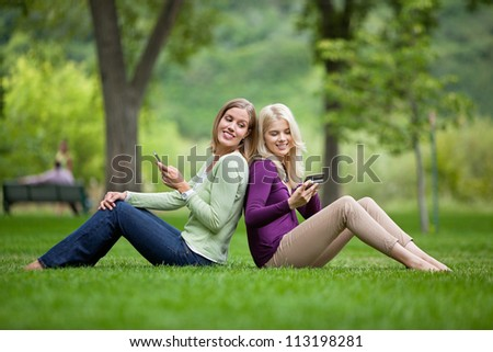 Side view of happy young female friends with cellphones sitting back to back in park - stock photo