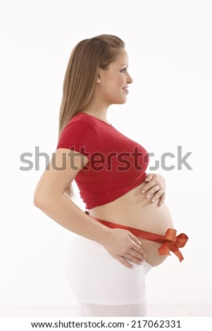 Side view of happy young pregnant woman with red ribbon around naked belly. - stock photo