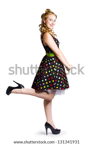 Side view of happy young woman in retro spotted dress, white background - stock photo