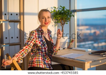 Side view of happy young woman working in home office, writing on paper. Female student learning material, doing task at workplace - stock photo