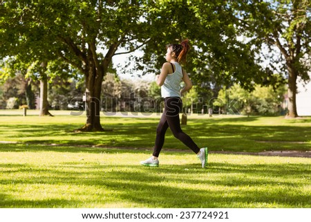 Side view of healthy and beautiful young woman jogging in park - stock photo