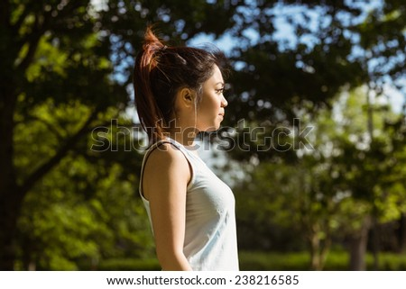 Side view of healthy and beautiful young woman standing in park - stock photo