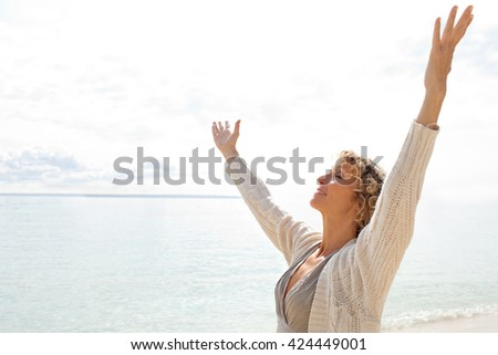 Side view of healthy senior woman in a transparent beach shore contemplating the sea, breathing raising open arms on sunny holiday destination beach, outdoors. Travel and lifestyle, vacation exterior. - stock photo