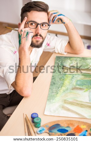 Side view of highly gifted painter while he is painting his picture. - stock photo