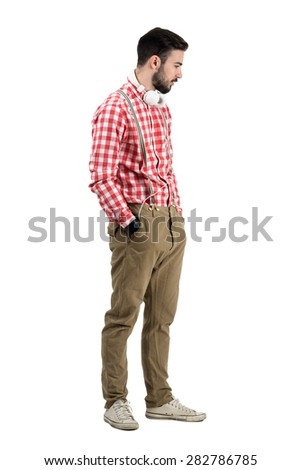 Side view of hipster dj with headphones around his neck looking down. Full body length portrait isolated over white background.  - stock photo