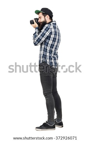 Side view of hipster in plaid shirt and baseball cap taking photo with dslr camera. Full body length portrait isolated over white studio background. - stock photo