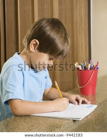 Side view of Hispanic boy concentrating on homework. - stock photo