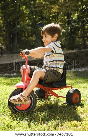 Side view of Hispanic boy riding red tricycle in grass. - stock photo