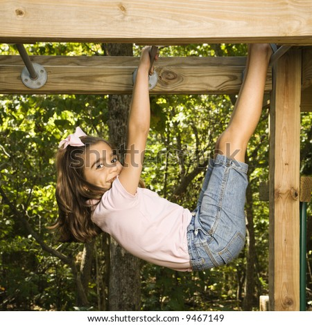Side view of Hispanic girl hanging by arms and legs from monkey bars smiling at viewer. - stock photo