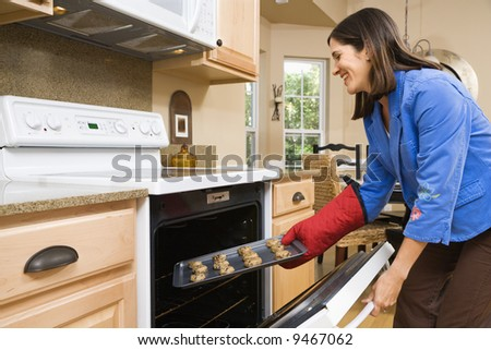 Side view of Hispanic mid adult woman putting cookies into oven. - stock photo