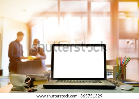side view of laptop with blank screen on table in modern office. - stock photo