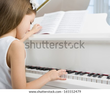 Side view of little girl in white dress playing piano. Concept of music study and arts