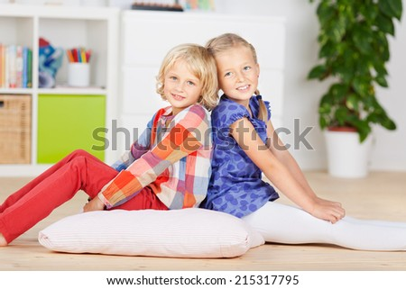 Side view of little girls sitting back to back on hardwood floor at home - stock photo