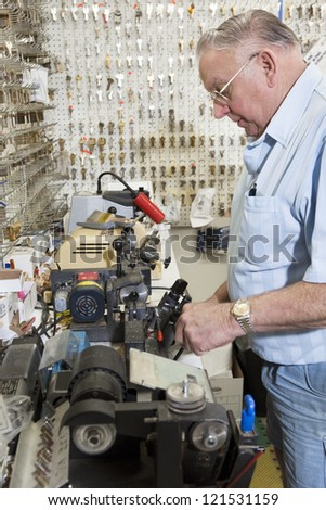 Side view of locksmith working in key store - stock photo