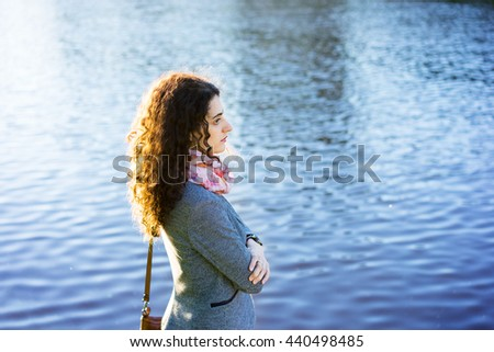 Side view of lonely young beautiful woman with lake on blurred background during summer. - stock photo