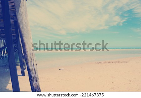 Side view of long jetty pier overlooking sandy beach with retro vintage filter. - stock photo