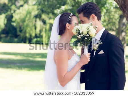 Side view of loving couple kissing behind bouquet in garden - stock photo